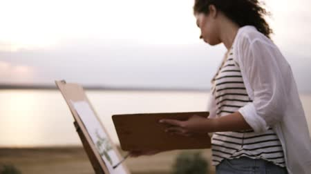 Side view of a lovely woman drawing outdoors on the meadow using an easel and palette. Blurred lake view on the background Vídeos
