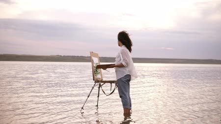 Accelerated shooting, a girl artist in the water till ankles draws a landscape using an easel and a palette. Curly girl on the background is lake, shes in casual clothes: jeans and a white shirt