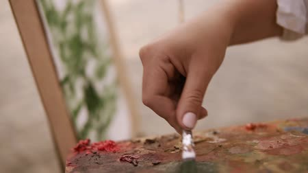 холст : Close up of a artist females hand mixing paints on palette and applies it on her surface on easel. Working process. Outdoors