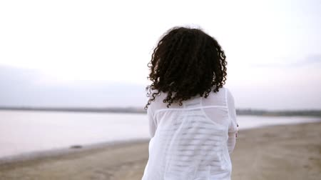 yalınayak : Close up side footage of an attractive young woman walking by seaside in water, wearing a white shirt. Curly brunette girl in cloudy morning walking outdoors Stok Video