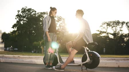 electro : Young male and female are have time together outdoors. Boys sitting on an electro mini bike and smiling. The girl in sunglasses stands near and talks. Sun shines on the background Stock Footage