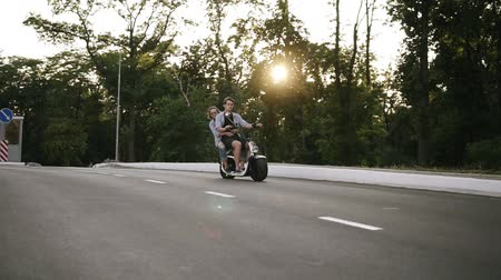 Two friends-couple are riding on an electro minibike by road. Happy, freedom. Young, beautiful couple having fun Vídeos
