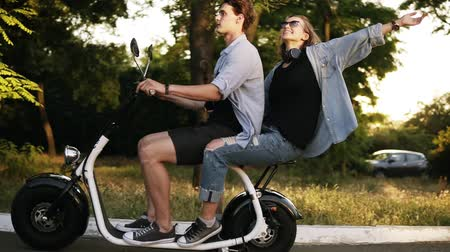 A happy couple riding on electro bike in street on summer day. Beautiful girl and her boyfriend enjoying their time. Park territory Vídeos