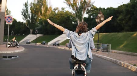 выражающий : Rare view of a young couple riding an electric bike in the green park. Girl in a blue shirt with outstretched hands. Feeling free and happiness Стоковые видеозаписи