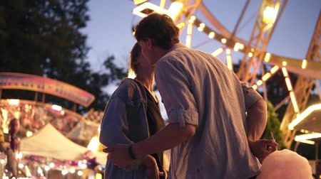 Low angle view of a gorgeous young couple in amusement park at night. Hadsome man surprised his girlfriend with a cotton candy. Tenderness, kissing, dating Vídeos