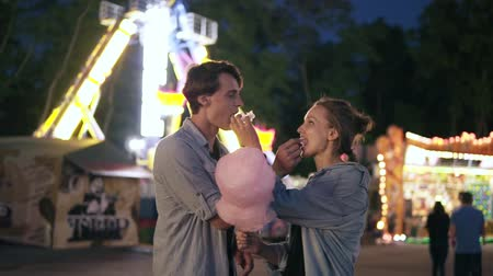 Young hipster couple are having time together in the amusement park at night. Feeding each other with pink cotton candy. Front view Vídeos