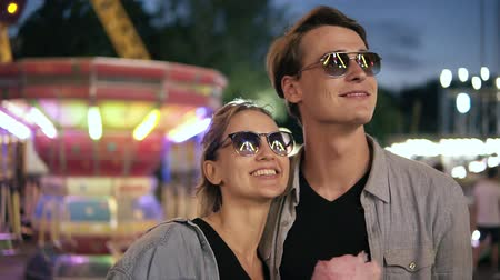 Portrait of a young, cheerful hipster couple in sunglasses are looking at attractions light. Happy, smiling young people at funfair at night