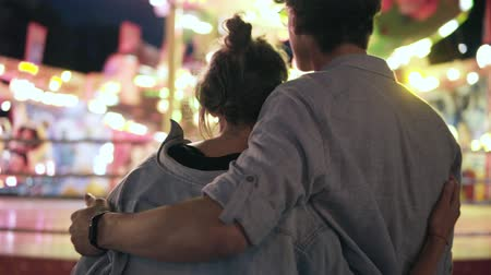 Stylish hipster young couple are standing and looking for at amusement park. hugging. Wearing blue similar shirts and sunglasses. Footage from the backside