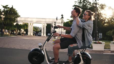 Young couple on dating riding an electronic minibike on the street. Wearing casual. Blonde lady closes his boyfriends eyes while riding. Daytime