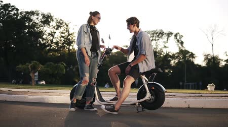 Two young stlylish friends are hanging out together. The boy is sitting on bike and talking to a beaitiful blonde girl in front. Happy, carefree, smiling Vídeos