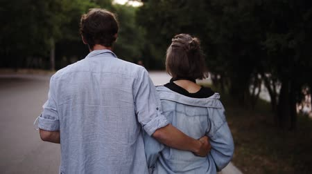 Traking footage of a young couple both in blue similar shirts are walking bonding by park. Romance, calmness, dating. Slow motion Vídeos