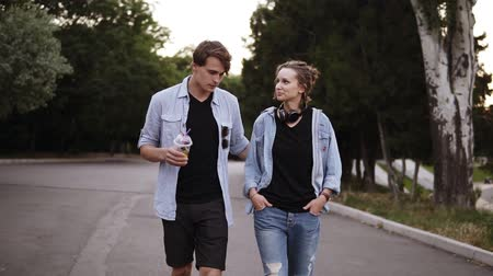 Beautiful young friends both in black T shirts and blue shirts are walking by park in the evening dusk. Talking, dating, summer time. Front view