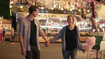 посещающий : Beautiful young couple visiting funfair, smiling, holding hands walking and eating cotton candy, night outdoors. Man and woman enjoying day out activities, recreation leisure lifestyle