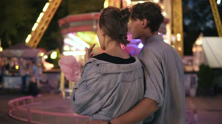 Backside view of a young dating couple walking by funfair at night, eating cotton candy. Both in similar blue shirts. Amusement park, loving pair,hugging Vídeos
