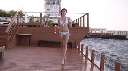 fulllength : A beautiful long-legged girl in a light swimsuit walks on the pier barefoot with a glass of cocktail in hand. Seaside. Front view Stock Footage