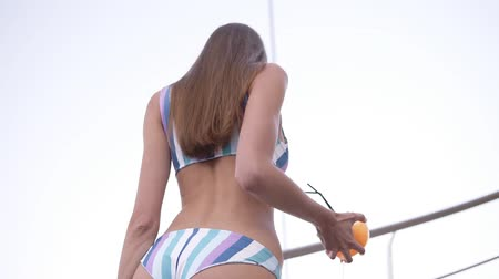 Low angle footage from the back of a seductive, sexy woman in bikini going upstairs with glass of orange cocktail. Daytime, seaside, summertime Vídeos