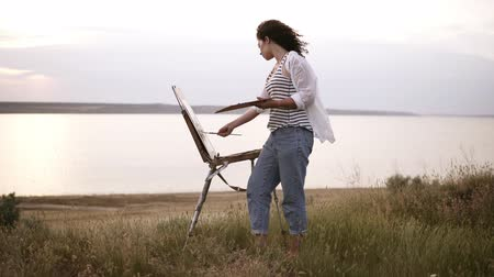 Full length footage of a beautiful girl in white shirt and jeans working outdoors. Paints using an easel and oil paints on the meadow in front the lake. Wind blowing, morning