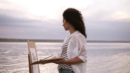 Outstanding view of a young curly brunette artist in working process, standing in the water with easel and drawing a picture with surrounding landscape. Outdoors Vídeos