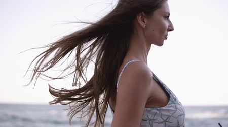 fulllength : Close up view of a attractive, longhaired brunette in bikini walking by pier. Wind blowing, waves her hair. Slender woman has a leisure time near the sea, with cocktail