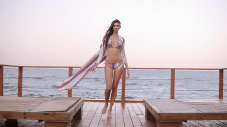 fulllength : Attractive, confident, fashionable woman in bikini and tunic walks through wooden lounge area near the sea. Front view, full length