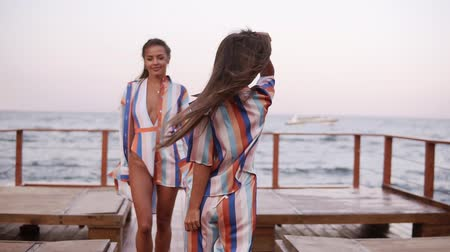 same : Front view of a gorgeous long legged tanned women walking by wooden seaside area. Dressed in clothes in the same style - sil colorful summer clothes. Windy, summer, daytime Stock Footage