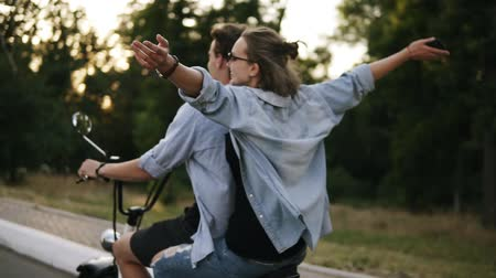 выражающий : Two friends riding on electricbike in the park. Young beautiful girl in sunglasses riding with her boyfriend. Stretches out her hands, feeling freedom, joy