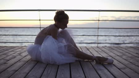 laços : Close up of a ballet dancer ties up the pointe. Young woman sitting on embankment. Womans feet in pointe shoes. Morning dusk