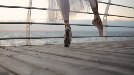 tiptoe : Close up of a ballet dancers feet as she practices point exercises. Ballerina elegantly walks by the embankment in white pointe. Slow motion