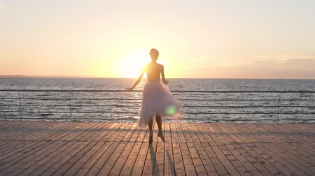 набережная : Graceful girl practicing ballet on the sidewalk near the sea , slow motion , does pirouettes. Morning sunrise