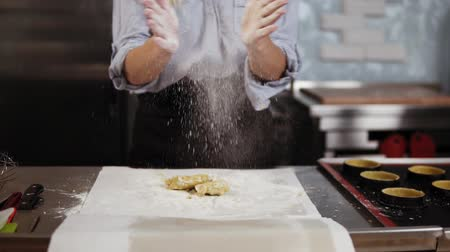 baker : A pretty caucasian blonde confectioner kneads pastry dough on a working surface. Smiles, shakes off flour from hands clapping. Front view, slow motion