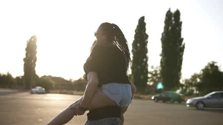 carinho : Young couple having fun on summer on an empty parking zone with boyfriend giving piggyback ride to girlfriend. Smiling, cheerful young people. Sun shining