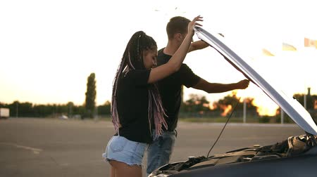 hádka : Side view of a young couple stopped while their road trip on the parking zone. Boy open up the car hood andpointing on the engine problem Dostupné videozáznamy