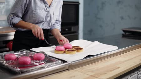 acabamento : Confectioner woman working on modern kitchen. Preparing modern, french desserts - mousse with pink mirror glaze putting on top baked tartles. Close up footage