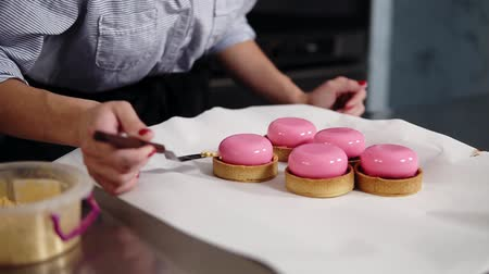 top chef : Close up footage of a confectioner decorating pink icing desserts. Desserts are on the working table, covered with white piece of paper. Indoors