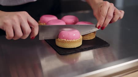 желатин : Womans hands cut the french dessert with pink mirror glaze on working surface on the kitchen. Pink cakes. Close up view