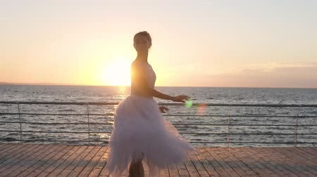 skok : Young beautiful woman is dancing wearing white tutu on sunrise or sunset. Performing classic ballet pas. Outdoors. Seaside Wideo