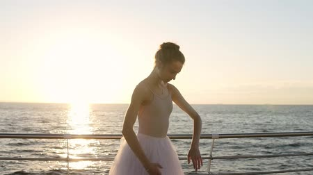 pirouette : Ballerina stretches on seaside, graceful girl practicing ballet pas, hands exercises. Morning sun rays on the background. Accelerated footage Stock Footage