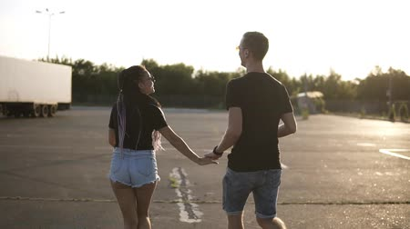 romantik : Young, cheerful couple having fun together on a parking zone. Holding hands, whirling, laughing. Wearing denim shorts and black T shirts. Sun shines on the background Stok Video