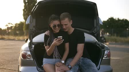 genç yetişkinler : Beautiful, young couple spending time together. Sitting in open car trunk, embracing and looking to the smarphone. Both in black T shirts, smiling, happy