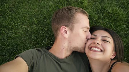dinlenmek : Young in love heterosexual caucasian couple resting outdoors in park on lawn, green grass lying in embrace and making selfie photo on smartphone camera. Blonde happy man kissing her girlfriend. Top view Stok Video