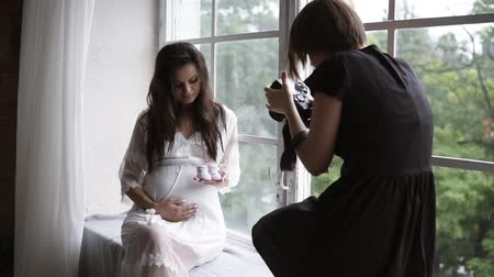 sill : Beautiful young pregnant photo model in white peignoir posing for female photographer while sitting next to the window in bright room Stock Footage