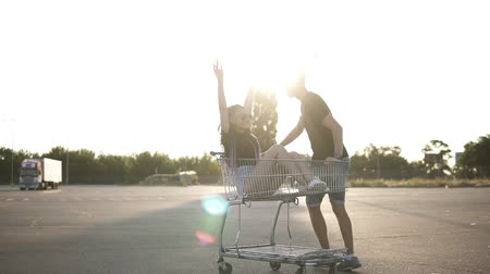 heyecan verici : Man pushing shop cart with a girl inside. Girl with a dreadlocks. She is lauging, exciting and raising hands up. Sun shines on the background