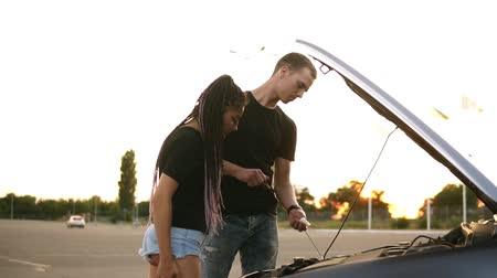 hádka : Side view of a young couple stopped while their road trip on the parking zone. Young man in black T shirt checks the oil level, his girlfriend with dreadlocks standing near the open car hood. Parking zone