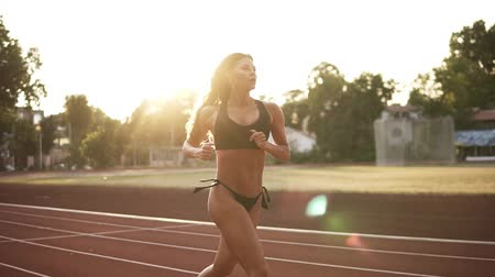 závodní dráha : Attractive woman in black bikini jogging on the racetrack on the stadium. Long haired brunette runner working out outdoors in the morning