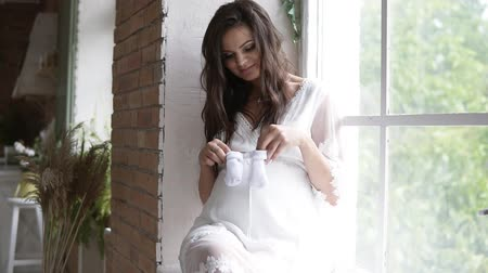 booties : Pregnant, beautiful woman sitting on the sill by the window. Holding babys booties or socks, making little steps on her pregnant belly