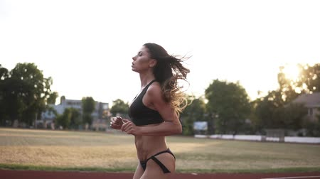 versenypálya : Caucasian sport model with beautiful body in black bikini running on the racetrack on the stadium. Long haired brunette working out outdoors Stock mozgókép