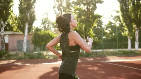 legginsy : Fit woman in black sport bra and shirt running outdoors. Brunette girl with pony tail happilly jogging. Sunlight Wideo