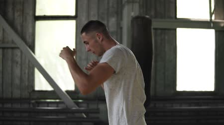 puncs : Side view of strong young man in sport shorts and T shirts boxing and punching invisible opponent while training in gym, slow motion Stock mozgókép