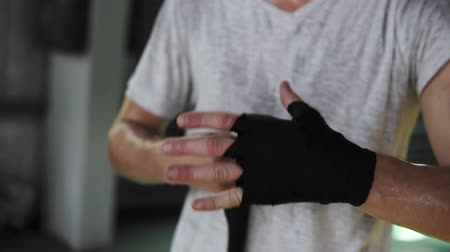 bandage : Closeup male hands of boxer wraps the black boxing bandages. Fists of fighter before the fight or training in sport gym Stock Footage