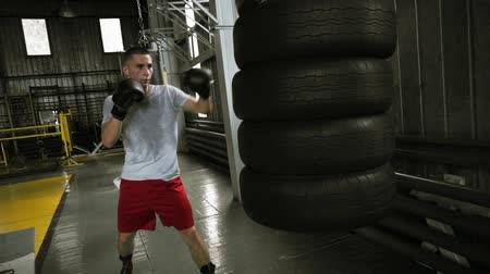 attacks : Male, aggresive boxer working out with punching bag made by car tyres. Working out in black boxing gloves in boxing studio Stock Footage